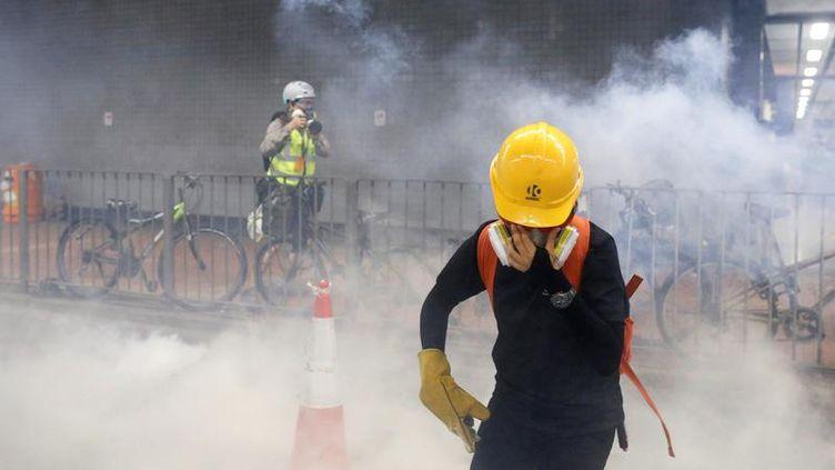 Un manifestant tente de se protéger après que la police a tiré des gaz lacrymogènes, le 10 août 2019, à Hong Kong. (THOMAS PETER / REUTERS)