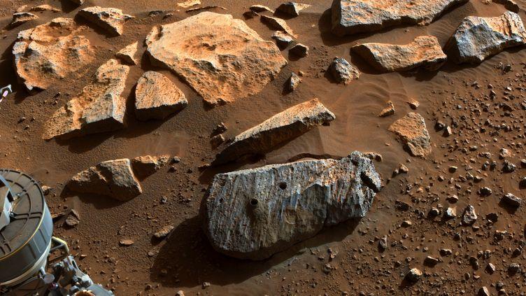 """10 septembre 2021 : la NASA a annoncé que le rover Perseveranceavait collecté un échantillon de terre martienne et l'image montre deux trous dans la roche volcanique surnommée """"Rochette"""". (HANDOUT / AFP)"""