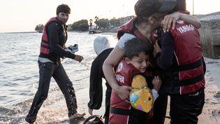 Une mère syrienne embrasse ses enfants à son arrivée sur une plage de l'île grecque de Kos, le 18 août 2015. (KONSTANTINOS TSAKALIDIS / SOOC / AFP)