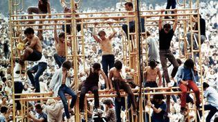 Woodstock, août 1969. Des festivaliers perchés au-dessus de la foule, un plan du documentaire de Michael Wadleigh consacré au festival et sorti en 1970. Ce documentaire a été récompensé par un Oscar. (WADLEIGH MAURICE / AFP)