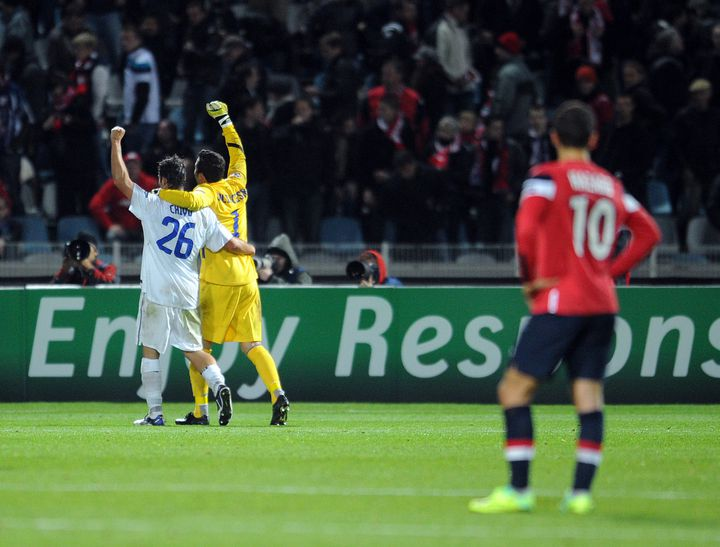 Le gardien de l'Inter Milan, Julio César (en jaune), et le défenseur milanais Christian Chivu (en blanc) célèbrent leur victoire face à Lille, le 18 octobre 2011, sous le regard du Lillois Hazard. (Philippe Huguen / AFP)