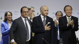 François Hollande, Laurent Fabius etBan Ki-moon, après l'annonce duprojet d'accord par la présidence française de la conférence de l'ONU, au Bourget (Seine-Saint-Denis), le 12 décembre 2015. (PHILIPPE WOJAZER / AFP)