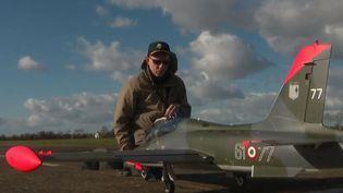 Marc Lumia aux côtés d'un avion de chasse en modèle réduit. (FRANCE 2)