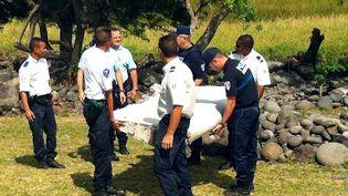 Des policiers et des gendarmes portent, le 29 juillet 2015, le débris d'avion retrouvé sur le littoral de la Réunion. (YANNICK PITOU / AFP)