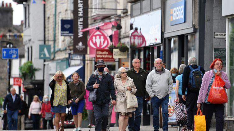 Des passants dans une rue de la ville de Kendal, dans le nord de l'Angleterre, le 21 juin 2021. (OLI SCARFF / AFP)