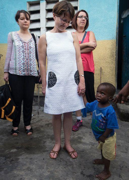 Une maman adoptive française tient par la main un petit garçon congolais à la maison de l'espoir à Kinshasa, le 26 novembre 2015. (PhotoAFP/Junior Kannah)
