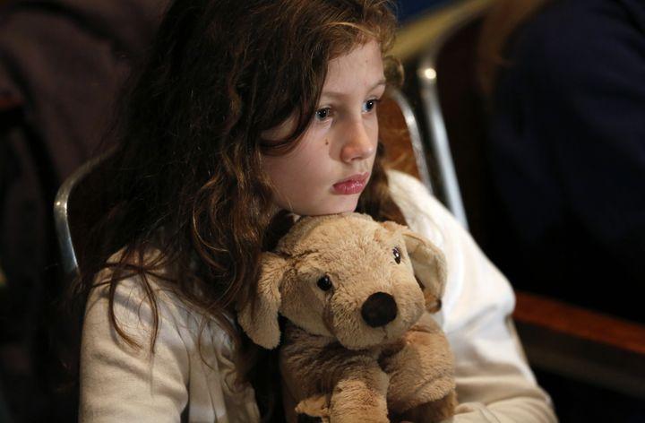 Une petite fille se recueille en la mémoire des 26 personnes tuées par Adam Lanza, à Newtown (Connecticut, Etats-Unis), le 16 décembre 2012. (KEVIN LAMARQUE / REUTERS)