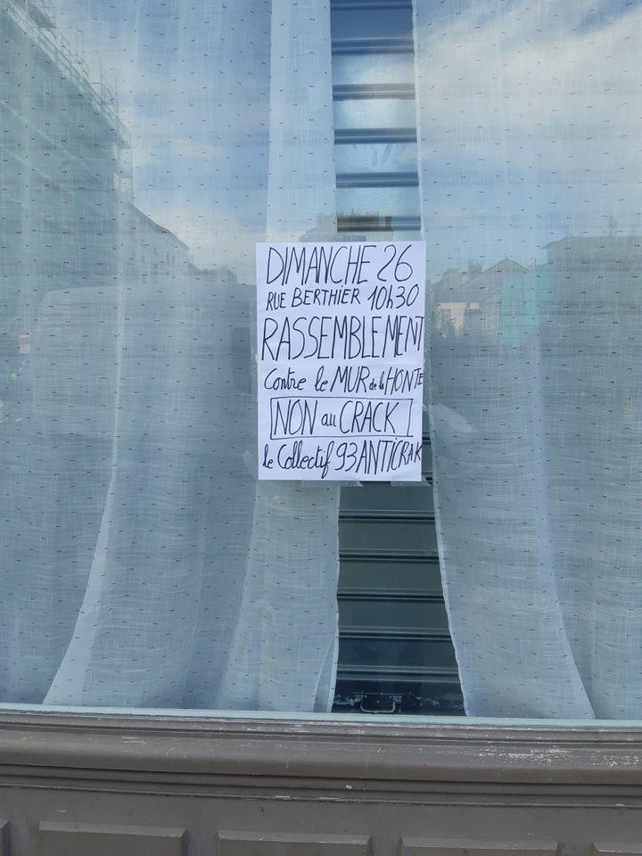 """Une affichetteà la fenêtre d'un riverain annonceun rassemblement contre le """"mur de la honte"""" à Pantin dimanche 26 septembre 2021. (JEROME JADOT / RADIO FRANCE)"""
