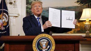 Donald Trump montre un document qui rétablit les sanctions contre l'Iran, après avoir annoncé le retrait des Etats-Unis de l'accord sur le nucléaire iranien, le 8 mai 2018, à Washington. (MARTIN H. SIMON / CONSOLIDATED NEWS PHOTOS)