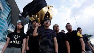 L'activisteJoshua Wong et une dizaine de militants drapent de noir un monument sumbole de Hong Kong rétrocédé à la Chine, le 26 juin 2017 (BOBBY YIP / REUTERS)