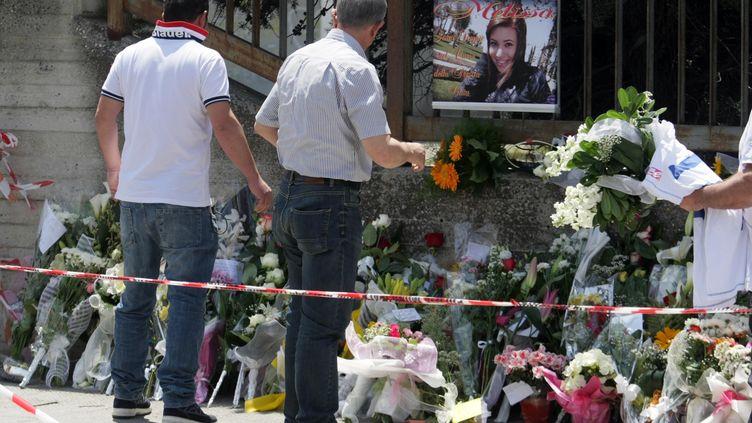 Des fleurs et des messages devant lelycée Francesca Morvillo Falcone à Brindisi (Italie) dimanche 20 mai 2012 après l'attentat quia tué samedi une lycéenne et blessé 5 de ses camarades. (CONTROLUCE / AFP)