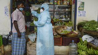 Une soignante fait passer un test Covid-19à un vendeur àChennai (Inde), le 10 avril 2021. (ARUN SANKAR / AFP)