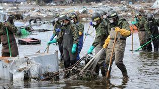 Les forces de défense japonaises recherchent des corps autour de Sendai, dans la préfecture de Miyagi. (AFP PHOTO / ROSLAN RAHMAN)