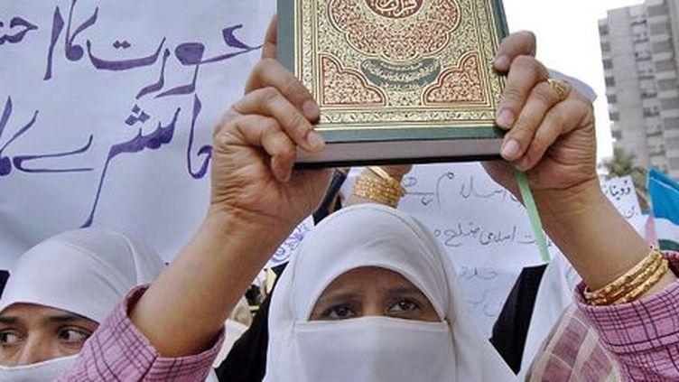 Militante islamiste brandissant le Coran lors d'une manifestation à Karachi (Pakistan) le 8 mars 2006. (ASIF HASSAN - AFP)