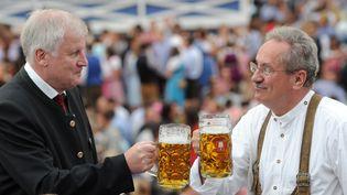 Le maire de Munich (Allemagne), à droite, trinque à l'occasion de l'ouverture de l'Oktoberfest, le 21 septembre 2013. (TOBIAS HASE / DPA / AFP)