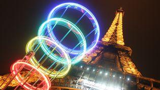 Les anneaux olympiques près de la tour Eiffel, le 12 mars 2005, à l'occasion de la candidature de Paris aux JO de 2012. (GABRIEL BOUYS / AFP)