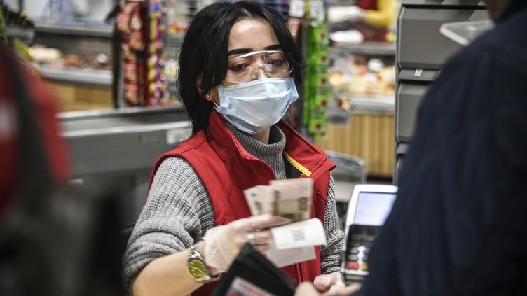 Une caissière porte un masque de protection et des gants, en pleine épidémie de coronavirus Covid-19, à Moscou, le 27 mars 2020. (ALEXANDER NEMENOV / AFP)
