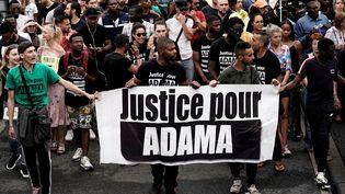"""Une banderole """"Justice pour Adama"""" tenue lors d'une manifestationà Beaumont-sur-Oise, le 20 juillet 2019. (KENZO TRIBOUILLARD / AFP)"""