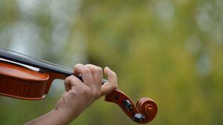 Une fillette joue du violon à Ankara (Turquie), le 18 juin 2017. (ALTAN GOCHER / AFP)