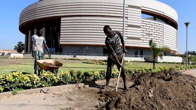Des jardiniers travaillent devant le musée des Civilisations noires (MCN) à Dakar le 27 novembre 2018. (SEYLLOU / AFP)