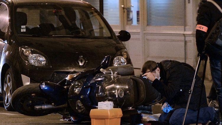 Des policiers examinent un véhicule retrouvé à terre devant l'hôtel Drouot, mercredi 19 février, après un braquage. (PIERRE ANDRIEU / AFP)