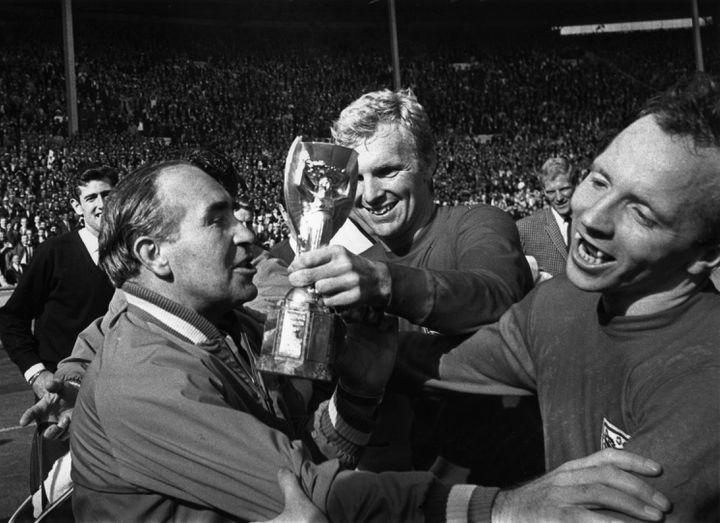 Le sélectionneur anglais Alf Ramsey célèbre la victoire de son équipe en Coupe du monde avec ses joueurs Bobby Moore (au centre) et Nobby Stiles (à droite), le 30 juillet 1966, à Londres (Royaume-Uni). (KEYSTONE / GETTY IMAGES )