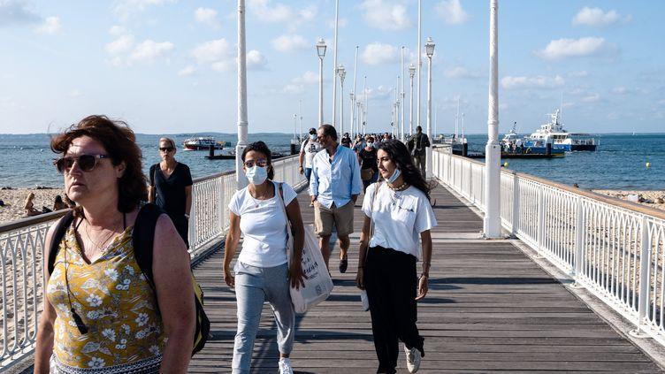 Des passants sur le littoral du bassin d'Arcachon (Gironde), le 26 juillet 2021. (VALENTINO BELLONI / HANS LUCAS / AFP)