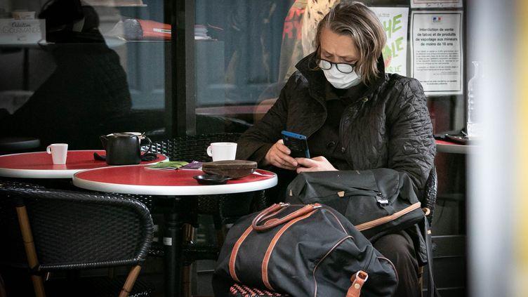 Une femme porte un masque à la terrasse d'un café, le 26 septembre 2019 à Rouen. (illustration) (LOU BENOIST / AFP)