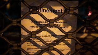 Un message expliquant les modalités de commande en ligne sur la vitrine d'une librairie parisienne, fermée pendant le confinement, le 9 novembre 2020. (AMAURY CORNU / HANS LUCAS / AFP)