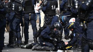 Un CRS est soigné par ses collègues après avoir été blessé dans des heurts avec les manifestants à Paris, le 1er mai 2019. (MARTIN BUREAU / AFP)