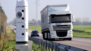 Un camion passe à proximité d'un radar censé collecter l'écotaxe, le 16 novembre 2013 à Lisieux (Calvados). (PHILIPPE HUGUEN / AFP)