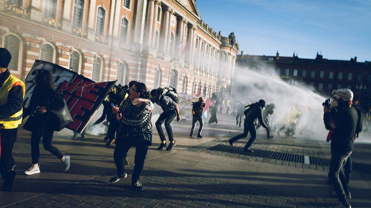 """Des manifestants dispersés par des canons à eau lors d'une manifestation de """"gilets jaunes"""", le 9 février 2019 à Toulouse. (VALENTIN BELLEVILLE / HANS LUCAS / AFP)"""