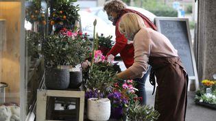Deux fleuristes péparent les arrangements de la Toussaint devant leur boutique à Mulhouse, le 29 octobre 2020pour leur dernier week-end d'ouverture avant le confinement. (VINCENT VOEGTLIN / MAXPPP)