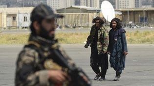 Des talibans marchent dans l'aéroport de Kaboul, le jour du départ des derniers soldats américains d'Afghanistan, le 31 août 2021. (WAKIL KOHSAR / AFP)