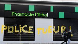 Un graffiti sur la façade d'une pharmacie, à Grenoble, le 2 mars 2019. (JEAN-PIERRE CLATOT / AFP)