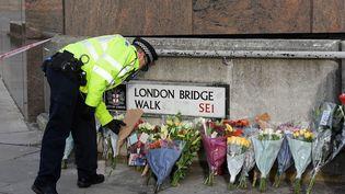 Unpolicier britannique dépose une gerbe de fleurs sur le London Bridge, dimanche 1er décembre, après l'attaque qui a fait deux morts.  (TOBY MELVILLE / REUTERS)