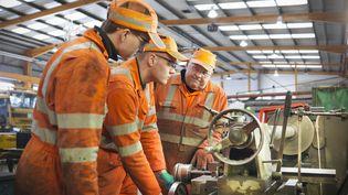 Un ingénieur enseigne son métier à des apprentis dans une usine de Doncaster (Royaume-Uni). (MONTY RAKUSEN / GETTY IMAGES / CULTURA RF)