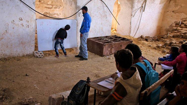 c'est mieux que rien. Ces enfants suivent un cours d'arithmétique dispensé avec les moyens du bord, dans une école de fortune. Venus de zones pro-gouvernementales, ils se trouvent actuellement dans la région de Deraa tenue par les rebelles. Cette «salle de classe» peu académique met un semblant de normalité dans la vie chaotique de ces enfants déplacés.  (MOHAMAD ABAZEED / AFP - Novembre 2016)