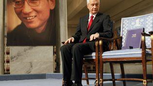 Le 10 octobre 2010 à Oslo, le président du comité NobelThorbjoern Jagland assis à côté de la chaise où aurait dû s'installer Liu Xiaobo, prix Nobel de la paix pour son combat en faveur de la démocratie. (HEIKO JUNGE / POOL)