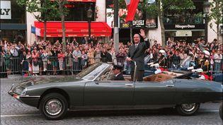 Debout dans une Citroën-Maserati (ouCitroën SM), le président de la République salue la foule massée sur les Champs-Elysées, le 17 mai 1995 à Paris, à l'issue de la cérémonie de son investiture.  (GEORGES BENDRIHEM / AFP)
