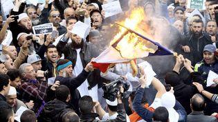 """Des manifestants qui protestent contre les caricatures de Mahomet publiées par """"Charlie Hebdo"""" brûlent un drapeau français, à Alger, la capitale algérienne, le 16 janvier 2015. (RAMZI BOUDINA / REUTERS)"""