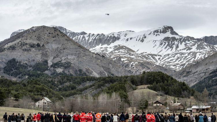 Des habitants et des membres de la Croix Rouge se recueillent devant une stèle en hommage aux victimes du crash de la Germanwings, au Vernet (Alpes-de-Haute-Provence), le 28 mars 2015. (JEFF PACHOUD / AFP)