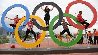Des personnes posent entre les anneaux des Jeux olympiques à Rio (Brésil), le 3 août 2016. (KIRILL KUDRYAVTSEV / AFP)