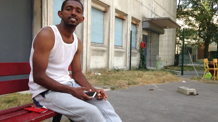Ahmed Salem, originaire de Libye, ne lâche jamais son téléphone. L'appareil lui permet de rester en contact avec ses amis et sa famille, comme ici depuis unlycée désaffecté du19e arrondissement de Paris, mercredi 5 août 2015. (FLORIAN DELAFOI / FRANCETV INFO)