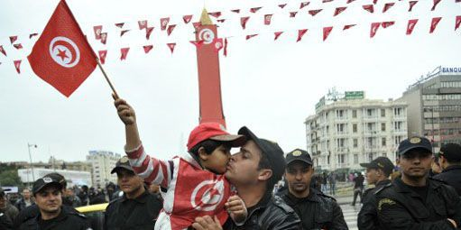 Un enfant, brandissant le drapeau tunisien, embrasse son père à Tunis lors des festivités marquant le second anniversaire de la révolution. (AFP - FETHI BELAID )
