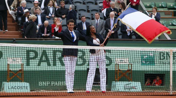 Le canoéiste Tony Estanguet (à gauche) transmet le drapeau de la France à l'épéiste Laura Flessel, le 10 juin 2012 à Roland Garros (Paris). (KENZO TRIBOUILLARD / AFP)