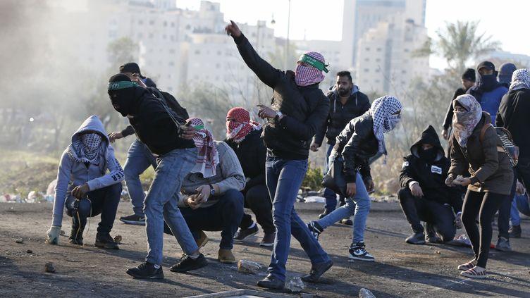 Des Palestiniens s'opposent aux forces de sécurité israéliennes, à Ramallah, le 8 décembre 2017. (ABBAS MOMANI / AFP)