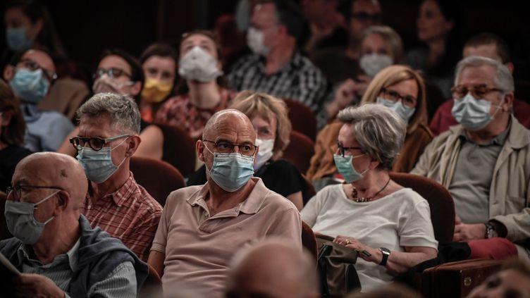 Des spectateurs portent un masque avant d'assister à une représentation au théâtre Antoine, à Paris, le 22 juin 2020. (STEPHANE DE SAKUTIN / AFP)