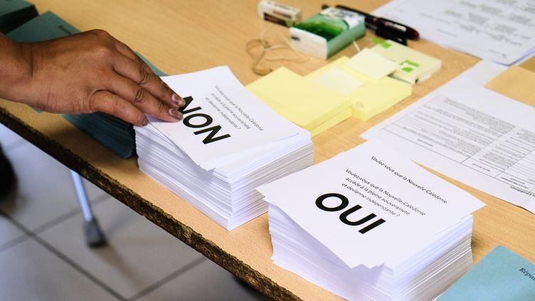 Une personne prend un bulletin de vote, le 4 octobre 2020, à Nouméa, lors du deuxième référendum sur l'indépendance de la Nouvelle-Calédonie. (THEO ROUBY / AFP)