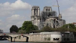 Une grue et des pompiers sur le site de la cathédrale Notre-Dame de Paris, après l'incendie qui l'a ravagée. (THOMAS SAMSON / AFP)